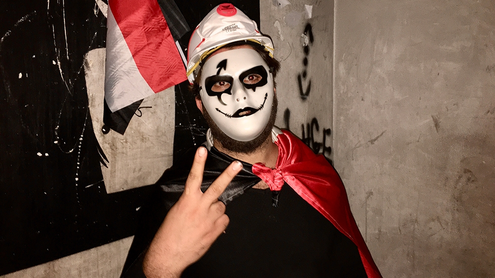 a man in a guy fawkes mask stands on the landing of the dark stairway leading up the tower [Sofia Barbarani/Al Jazeera]