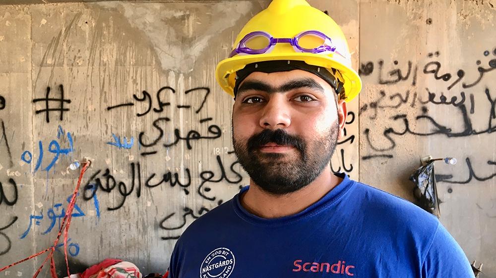 Abdullah stands inside one of the building's makeshift bedrooms  [Sofia Barbarani/Al Jazeera]