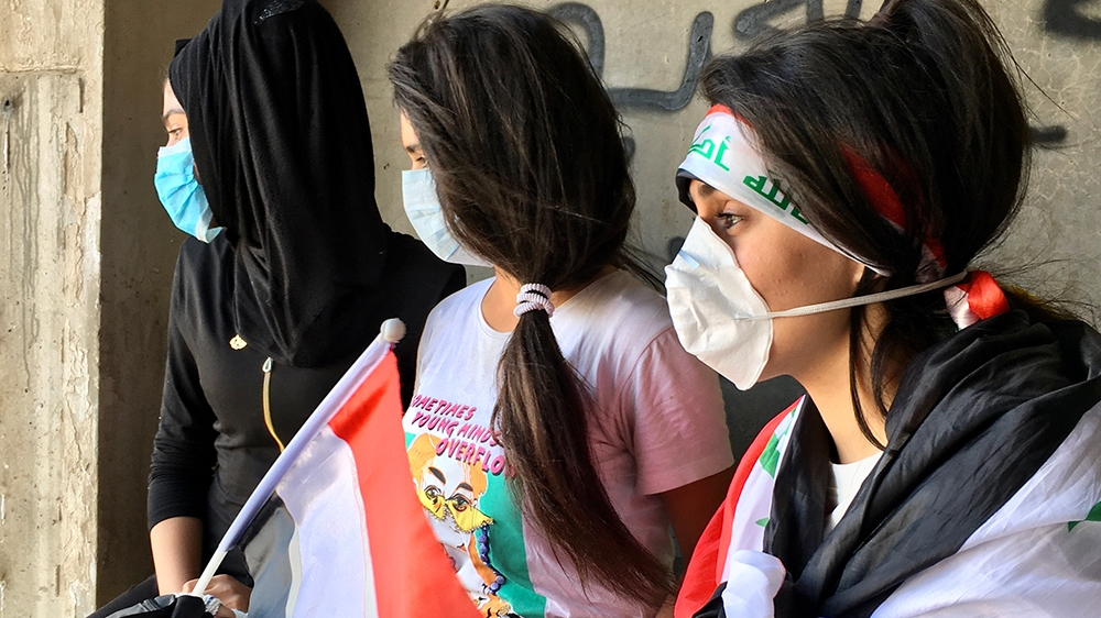 three young women look out into Tahrir square [Sofia Barbarani/Al Jazeera]