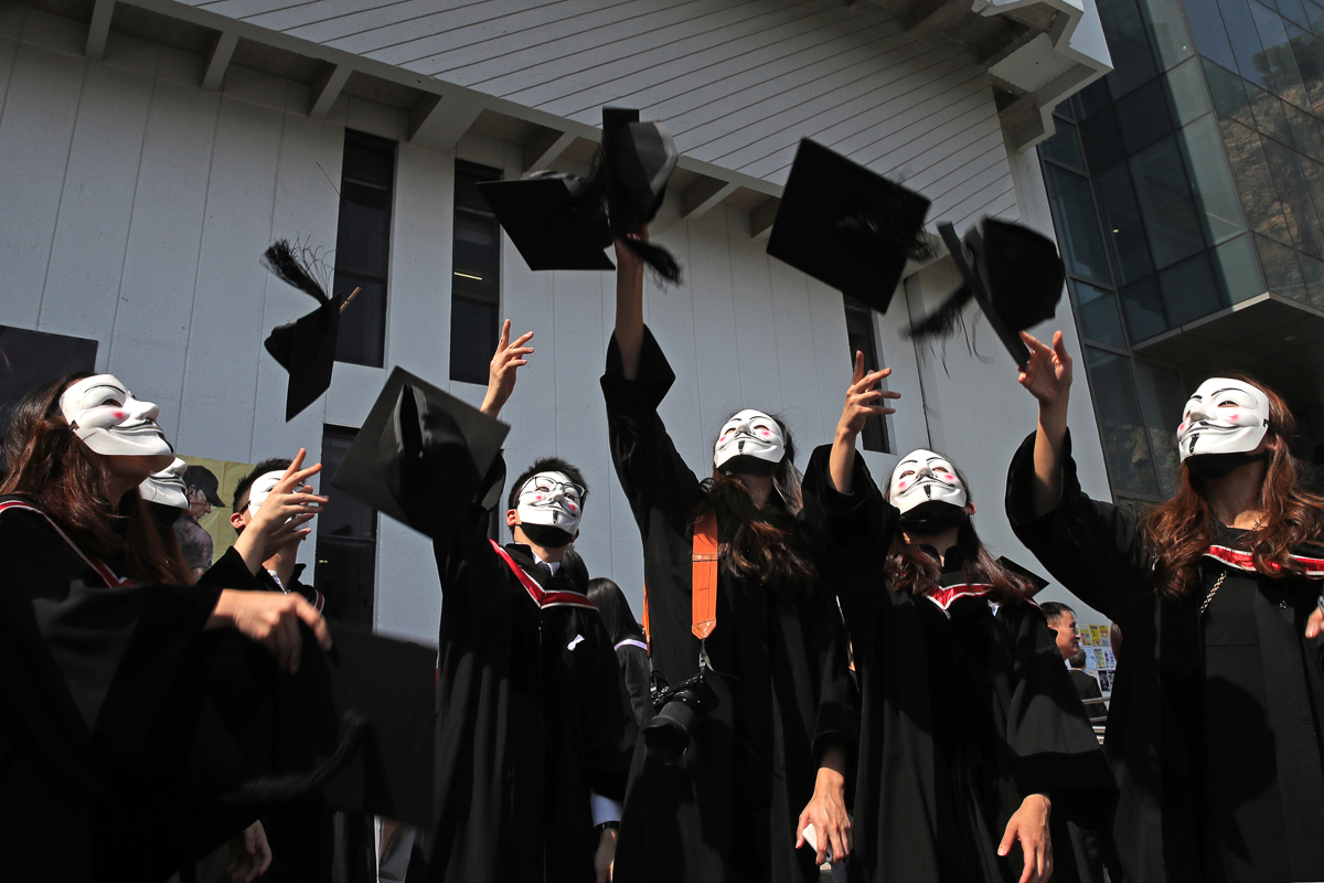 University students wearing Guy Fawkes masks throw their hats after their graduation ceremony at the Chinese University of Hong Kong. [Kin Cheung/AP Photo]