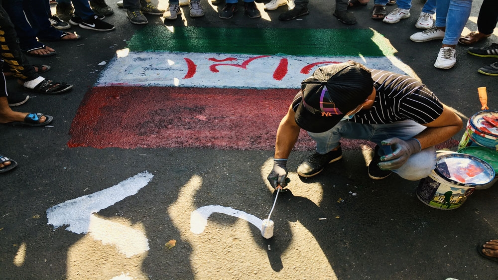 A protester in Baghdad paints at the site of a sit-in