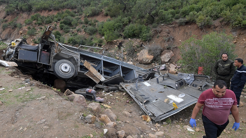 Tunisian security forces check the debris of a bus that plunged over a cliff into a ravine, in Ain Snoussi in northern Tunisia on December 1, 2019. - The bus, with 43 people on board had set off from
