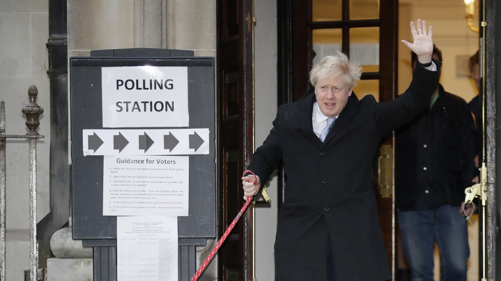 Britain's Prime Minister and Conservative Party leader Boris Johnson with his dog Dilyn leaves after voting in the general election at Methodist Central Hall, Westminster, London, Thursday, Dec. 12, 2