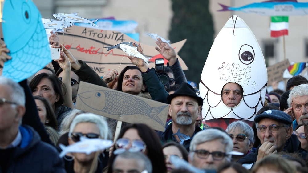 A demonstrator shows a sardine-shaped banner reading