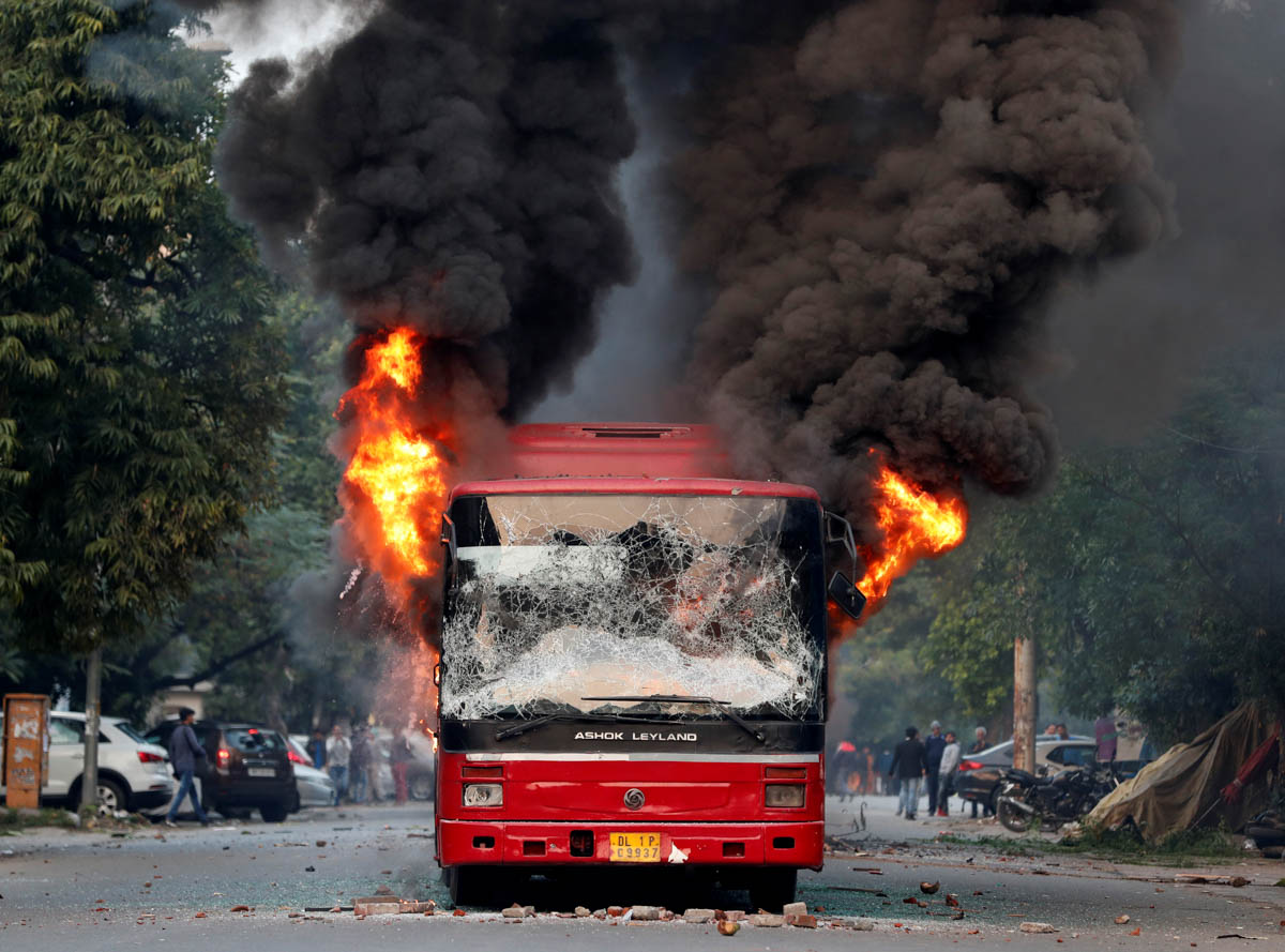 A burning bus after it was set on fire by demonstrators during a protest against a new citizenship law, in New Delhi, India. [Adnan Abidi/Reuters]