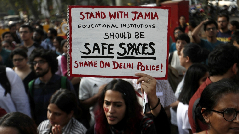 A woman holds a placard during a protest in solidarity with Jamia Millia Islamia university students after police entered the campus on Sunday in New Delhi, following a protest against a new citizensh