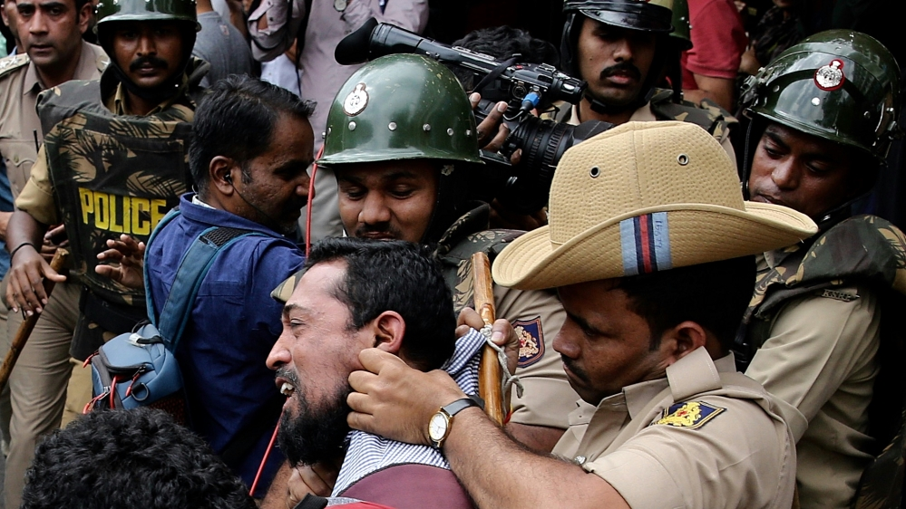 Indian policemen detain protesters during a protest in solidarity with Jamia Millia Islamia University students and against the Citizenship Amendment Bill (CAB) and National Register of Citizens (NRC)
