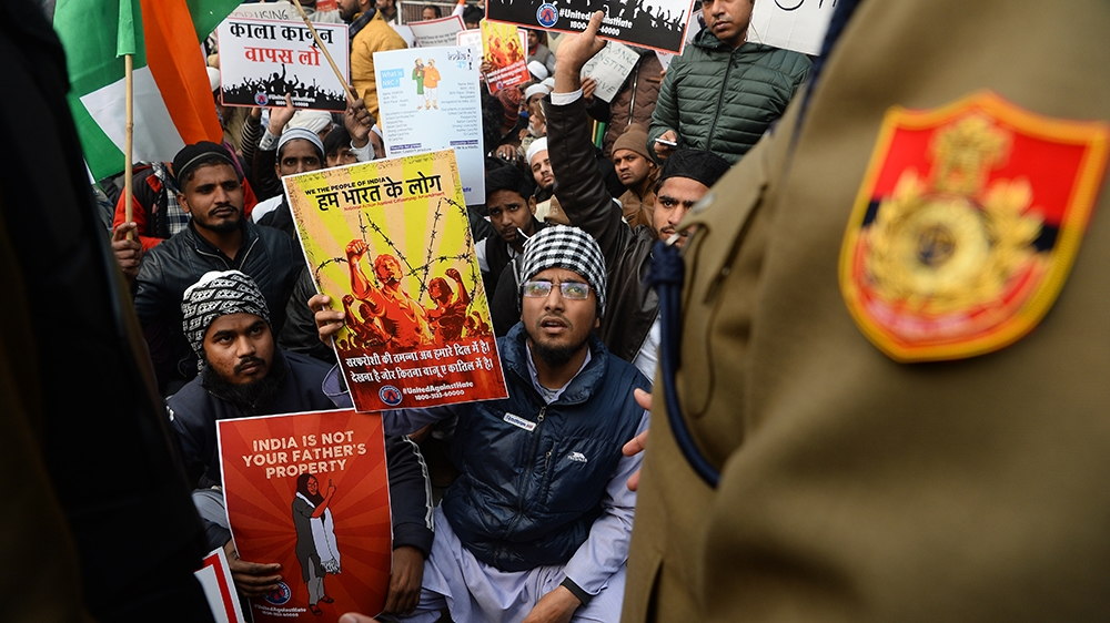 A policeman confronts protesters gathered for a demonstration against Indiai´s new citizenship law in New Delhi on December 19, 2019. - Big rallies are expected across India on December 19 as the tumu