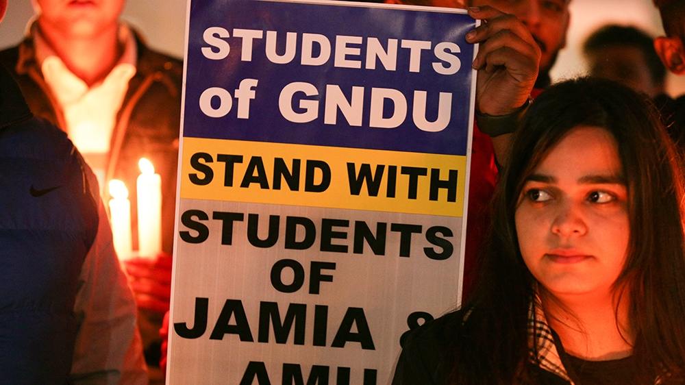 Activists of National Students' Union of India (NSUI) take part in a candle light vigil to show solidarity with Jamia Milia Islamia University and Aligarh Muslim University students and against Delhi