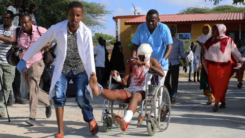 Paramedics and civilians assist a man injured in a car bomb explosion at a security checkpoint as he arrives to a hospital in Mogadishu