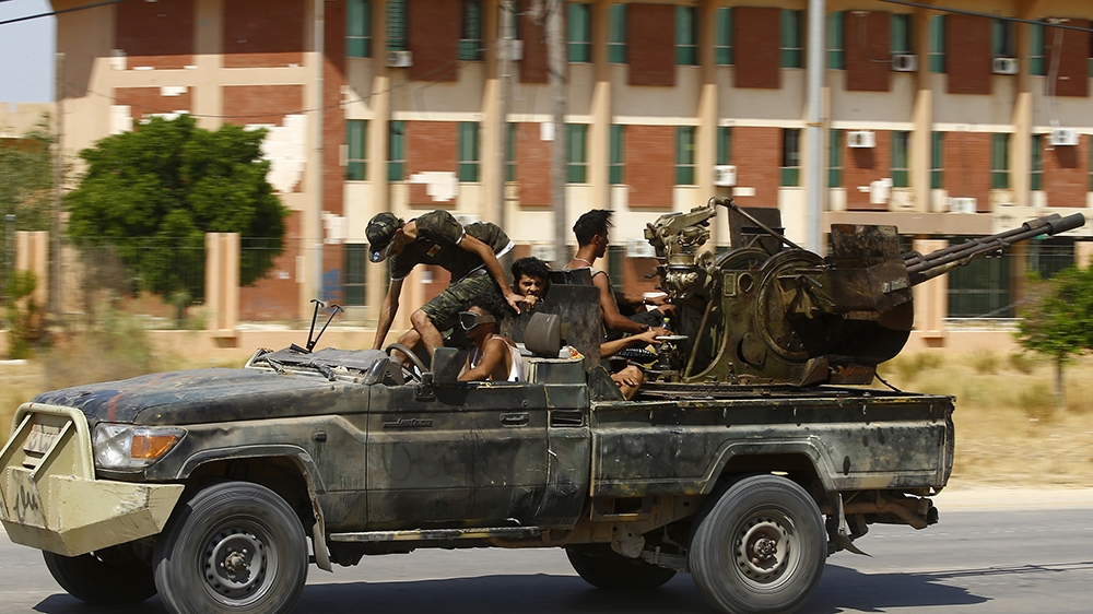 Fighters loyal to the UN-recognised Government of National Accord (GNA), geare transported on board of a military vehicle  during clashes with forces loyal to strongman Khalifa Haftar, in Espiaa, abou