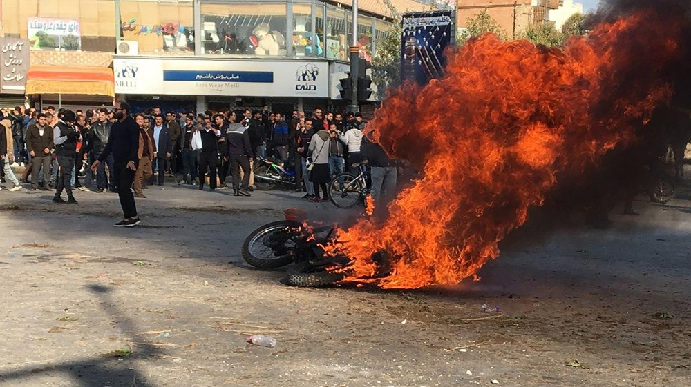 Iranian protesters gather around a burning motorcycle during a demonstration against an increase in gasoline prices in the central city of Isfahan, on November 16, 2019. [AFP]