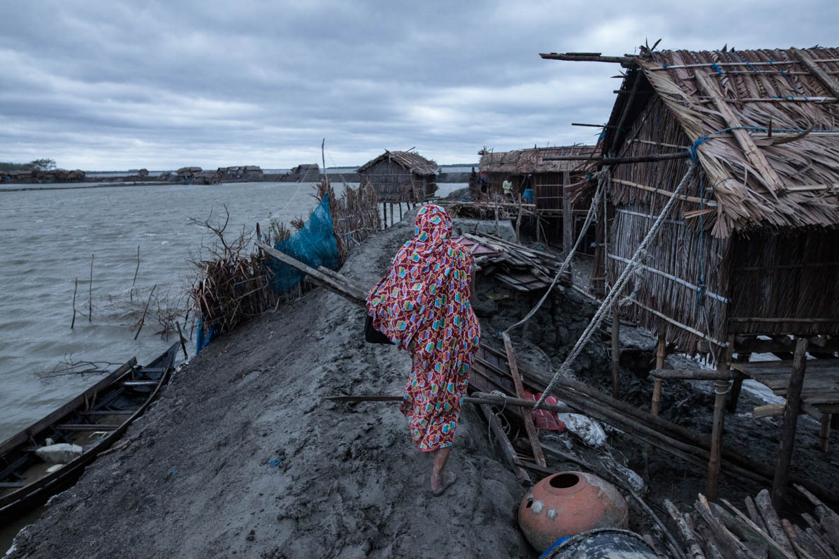 A woman returns home after Cyclone Fani hit the coastal area of Bangladesh in May.At least 17 people were killed in 10 districts. [Zakir Hossain Chowdhury/Al Jazeera]