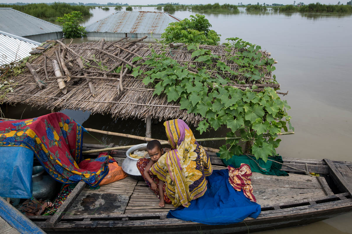 A mother and child sit on a boat near their submerged house on the banks of the Brahmaputra River in the Kurigram district. [Zakir Hossain Chowdhury/Al Jazeera]