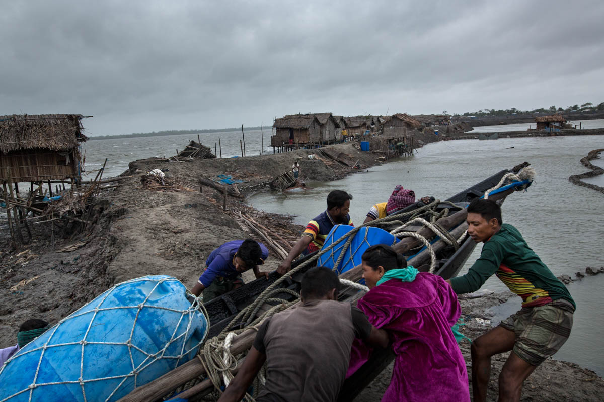 People try to save their boat during a cyclone near the Sundarbans area. Fishing in the river is the main source of income for people in the area. [Zakir Hossain Chowdhury/Al Jazeera]