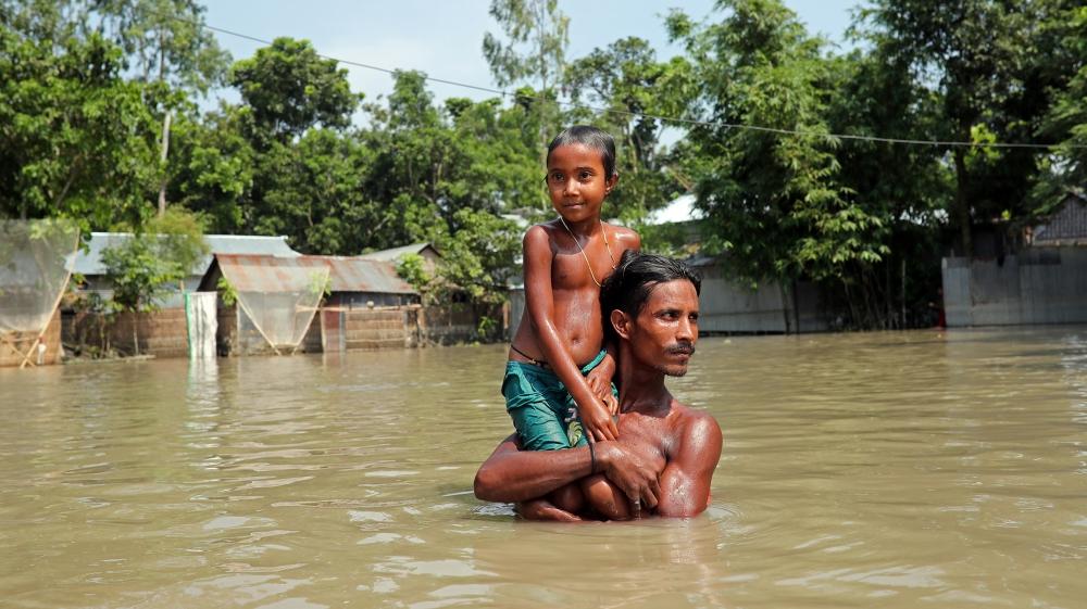 Flood-affected people wade through flooded water in Jamalpur, Bangladesh, July 21, 2019. REUTERS/Mohammad Ponir Hossain