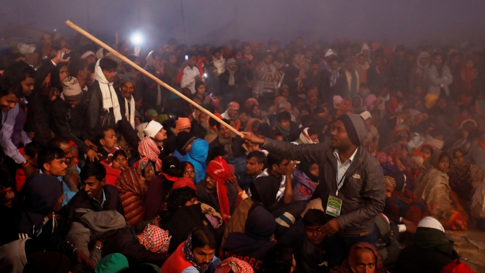 A volunteer controls a crowd using a stick during the ritual before the sacrificial ceremony of the