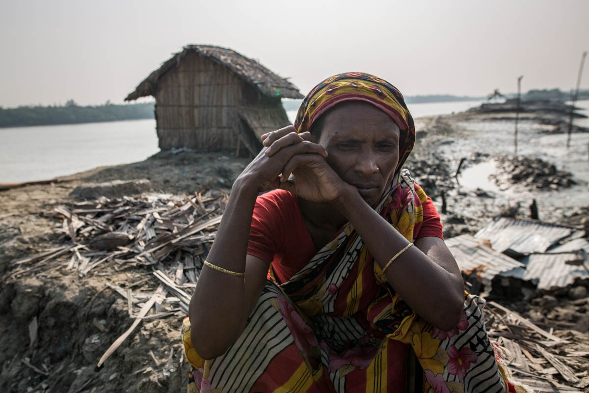 """Afia Begum, 46, in front of her temporary house near the Shibsha River in Khulna district. She has shifted her house five times because of storms and soil erosion in the Dacope area. """"I lost my house in Cyclone Fani. Now I am living in a bamboo house built on the river."""" [Zakir Hossain Chowdhury/Al Jazeera]"""