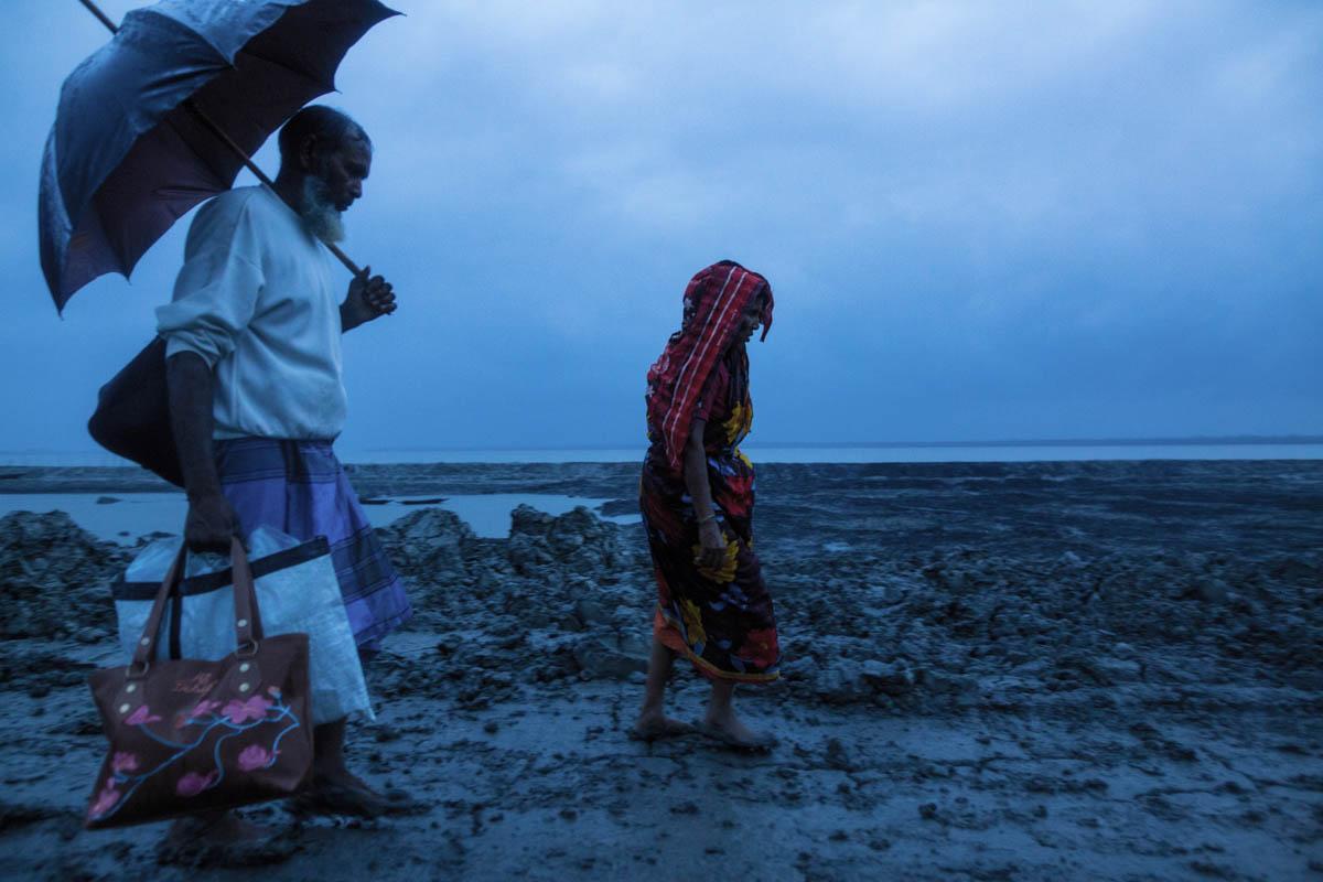 A family heads towards shelter before cyclone Fani hit coastal areas near the Sundarbans. The cyclone struck Bangladesh in May, causing damage worth around $63m. [Zakir Hossain Chowdhury/Al Jazeera]