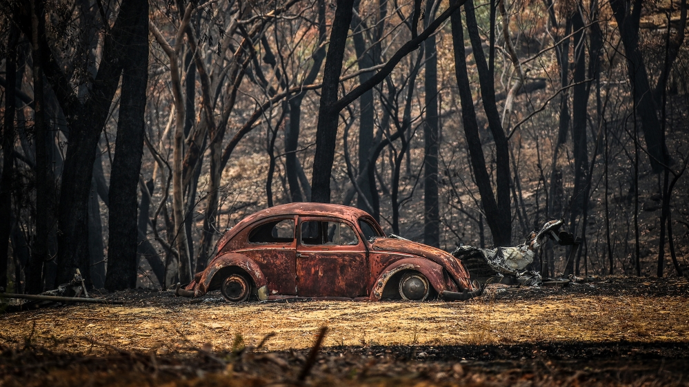 The remains of a car that was destroyed by bushfires sits near a home in the town of Balmoral on December 30, 2019 in Sydney, Australia. Firefighters have made the most of slightly cooler conditions o