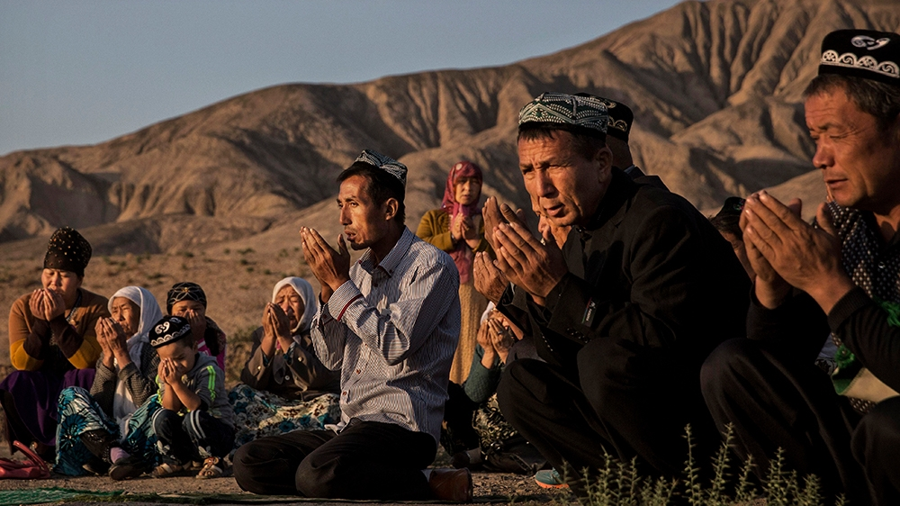 (CHINA OUT) A Uyghur family pray at the grave of a loved one on the morning of the Corban Festival on September 12, 2016 at a local shrine and cemetery in Turpan County, in the far western Xinjiang pr