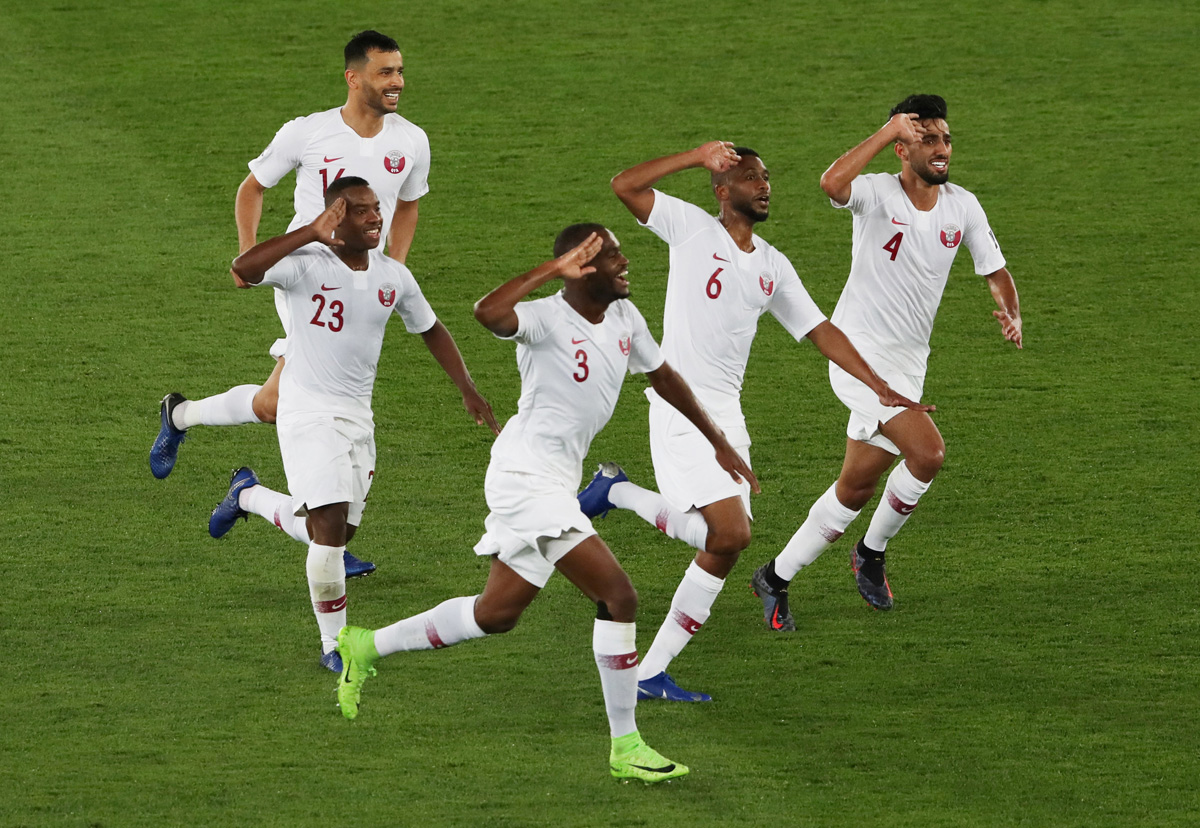 Qatar's Abdelaziz Hatim (center) celebrates with teammates after scoring their second goal. [Ahmed Jadallah/Reuters]