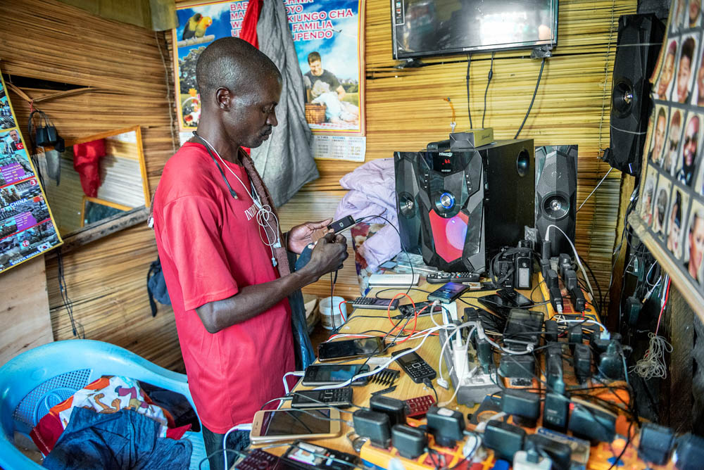 Daniel Obadha, 35, is a Kenyan electrician who has been running a barber shop and phone charging shop on the densely populated island for two years. 'I like to live on Migingo. Thanks to many customers coming not only from Kenya but also from Uganda and Tanzania, there is a lot of business and I earn much more money than I did on the mainland,' he said. [Jeroen van Loon/Al Jazeera]