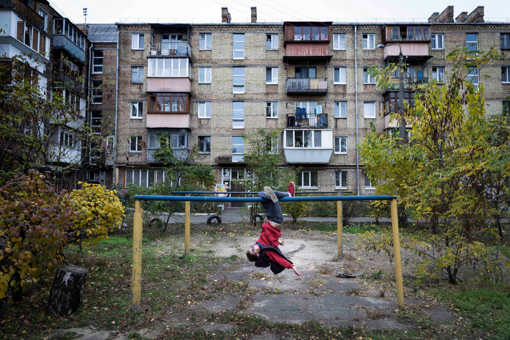 A boy plays in the backyard of a Soviet-era building on the outskirts of Kiev, Ukraine. [Erik Messori/CAPTA/Al Jazeera]