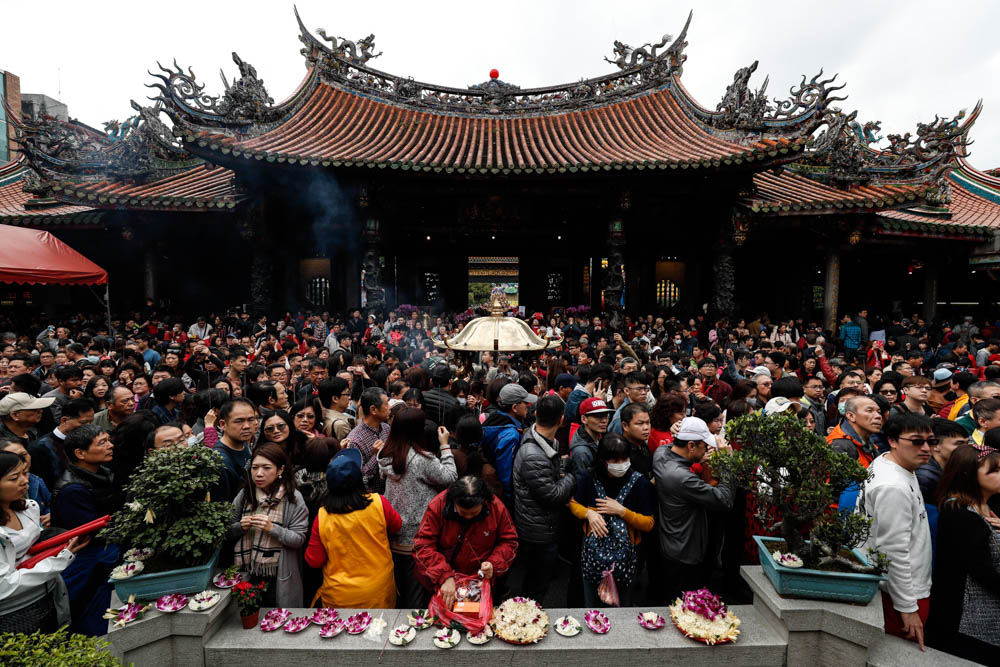 People pray and offer flowers and food inside the Lungshan Temple during the celebration in Taipei, Taiwan. [Ritchie B. Tondo/EPA]