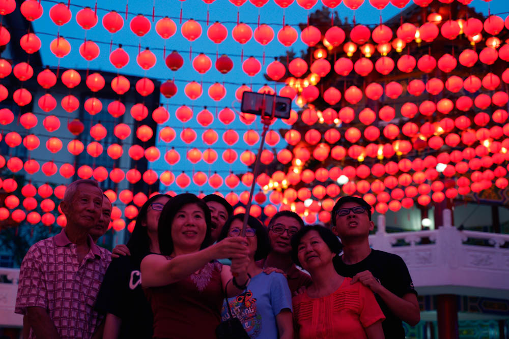 A group of ethnic Chinese Malaysians take a selfie by a temple in Kuala Lumpur, Malaysia. Chinese around the world will be celebrating the start of the Year of the Pig in the Chinese lunar calendar. [Yam G-Jun/AP Photo]