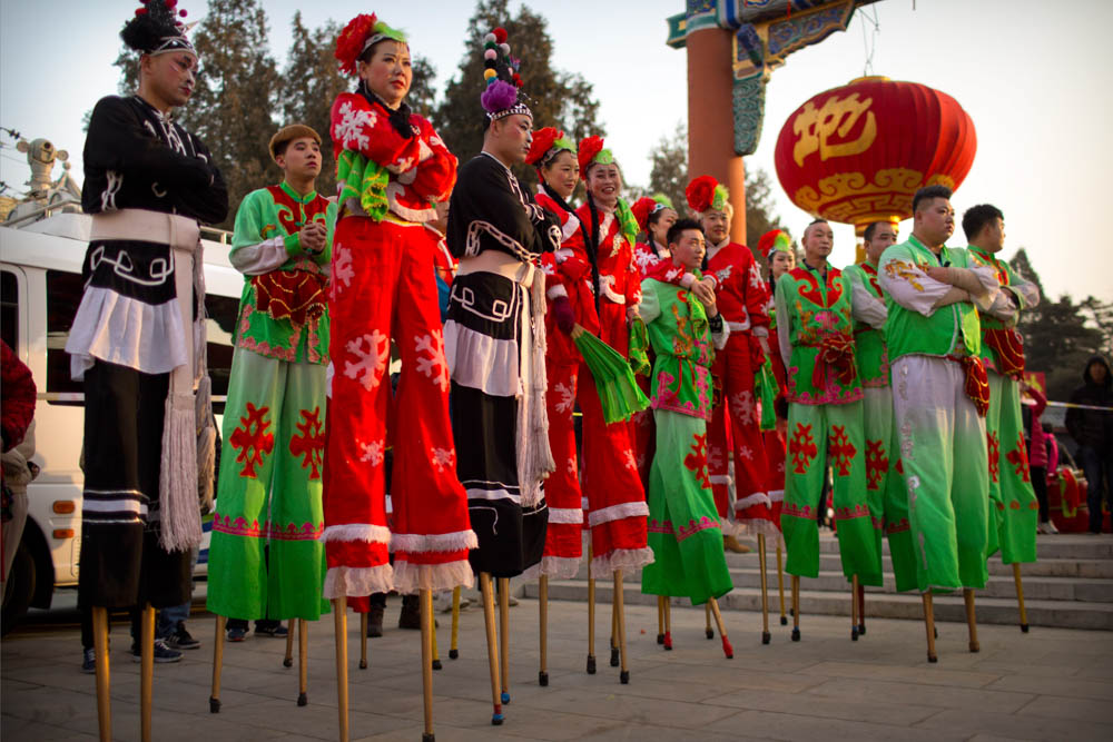 Performers on stilts watch a drum performance at Ditan Park in Beijing. During the holiday, which is also called Spring Festival, Chinese all over the world reunite with family members, visit friends and relatives, exchange gifts, give red envelopes of money to children, set off firecrackers and visit temples to pray for peace in the new year. [Mark Schiefelbein/AP Photo]