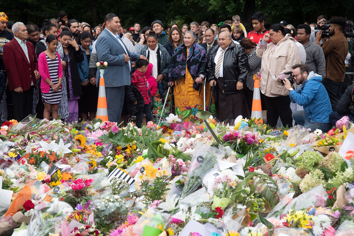 At a makeshift memorial in Christchurch, a steady stream of people laid flowers and lit candles, some standing quietly, others crying or visibly distressed. [Marty Melville/AFP]