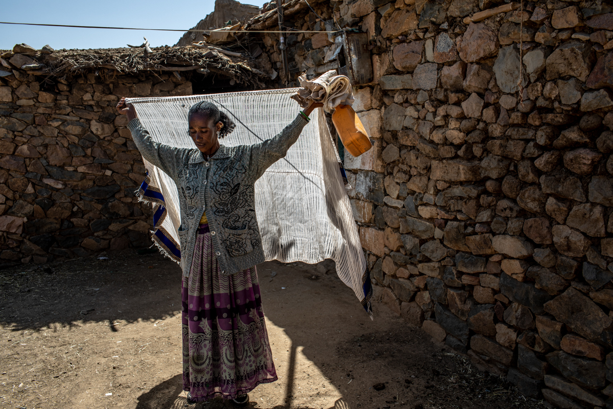 Birhan, a 40-year-old mother of four, sets off for a distribution point to collect her family's monthly rations in Hawzen. Birhan receives support from the Joint Emergency Operation Program, a USAID-funded food relief initiative. [Will Baxter/CRS]