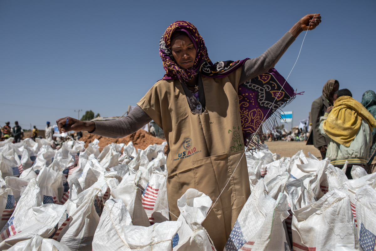 A woman opens bags of wheat at a distribution point in Hawzen district. 'This is a part of the world where the majority of families survive on what food they are able to grow. So even the smallest shifts in weather can leave these families with nothing,' said CRS's Matt Davis. [Will Baxter/CRS]