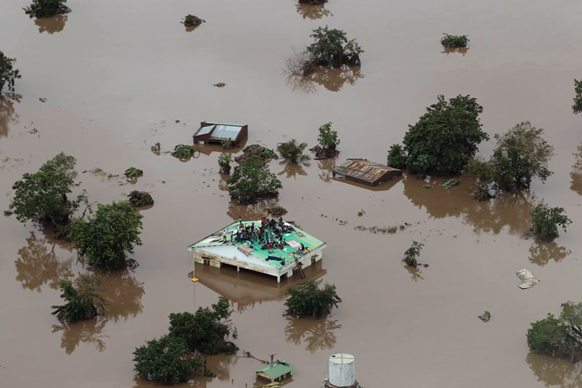 People on the roof of a submerged house in an area affected by cyclone Idai in Beira. The Red Cross said 90 percent of Beira and its surrounds are 'damaged or destroyed'. [Rick Emenaket/Mission Aviation Fellowship/AFP]