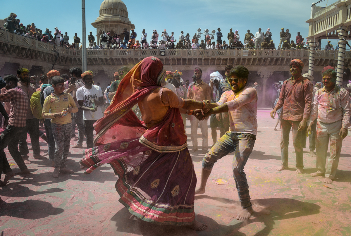 People covered in coloured powder dance as they celebrate Holi during a traditional gathering at a temple in Nandgaon village in India's Uttar Pradesh state