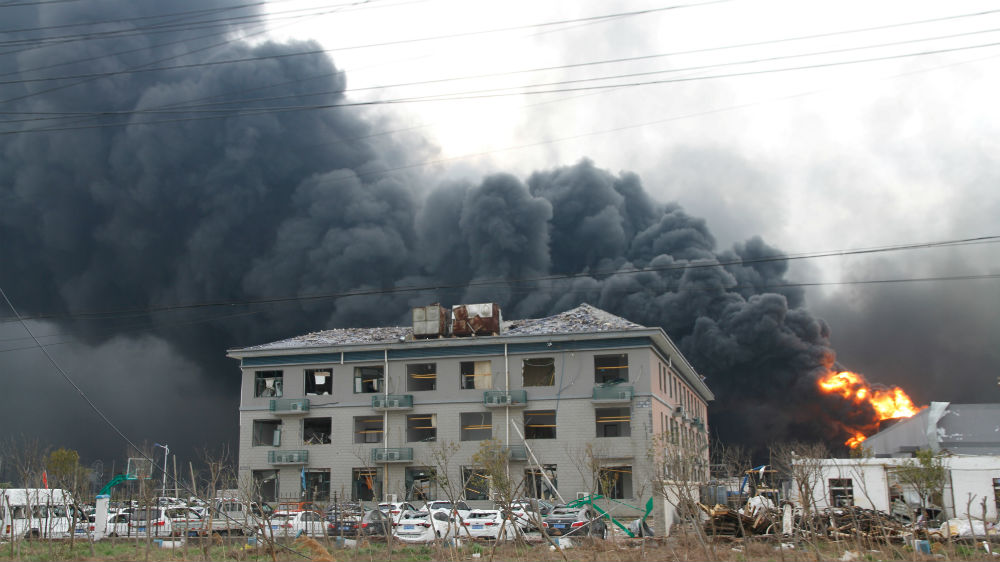 Smoke billows from fire behind a damaged building following the explosion