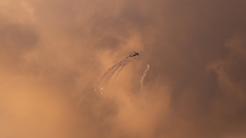 An Israeli Apache helicopter releases flares as it flies over the Gaza Strip