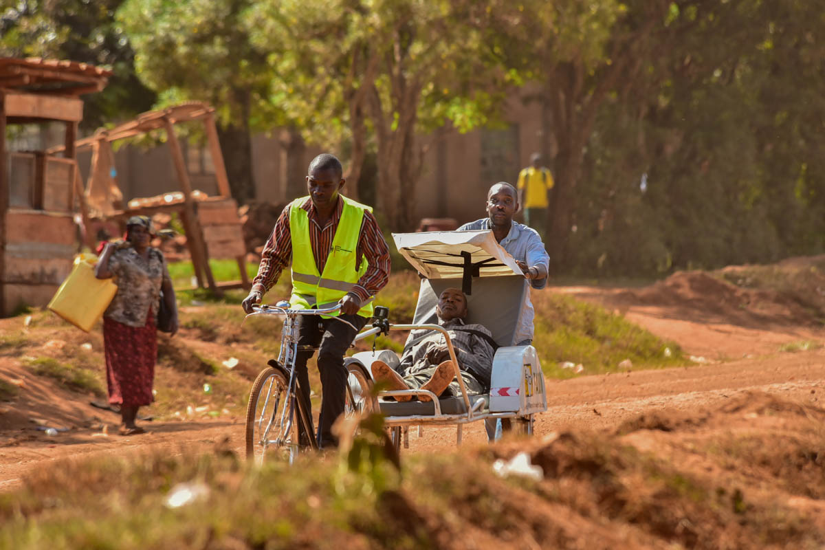 The bicycle ambulance service operates in areas where cars can not travel, with local workers ferrying people to health centres. [Nicholas Bamulanzeki/Al Jazeera]