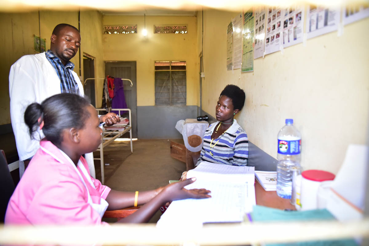 Sandra Naigaga (R) receives antenatal advice from Joshua Musomba and midwife Juliet Namuswa. Every day 15 women die in Uganda from childbirth and pregnancy-related issues. [Nicholas Bamulanzeki/Al Jazeera]