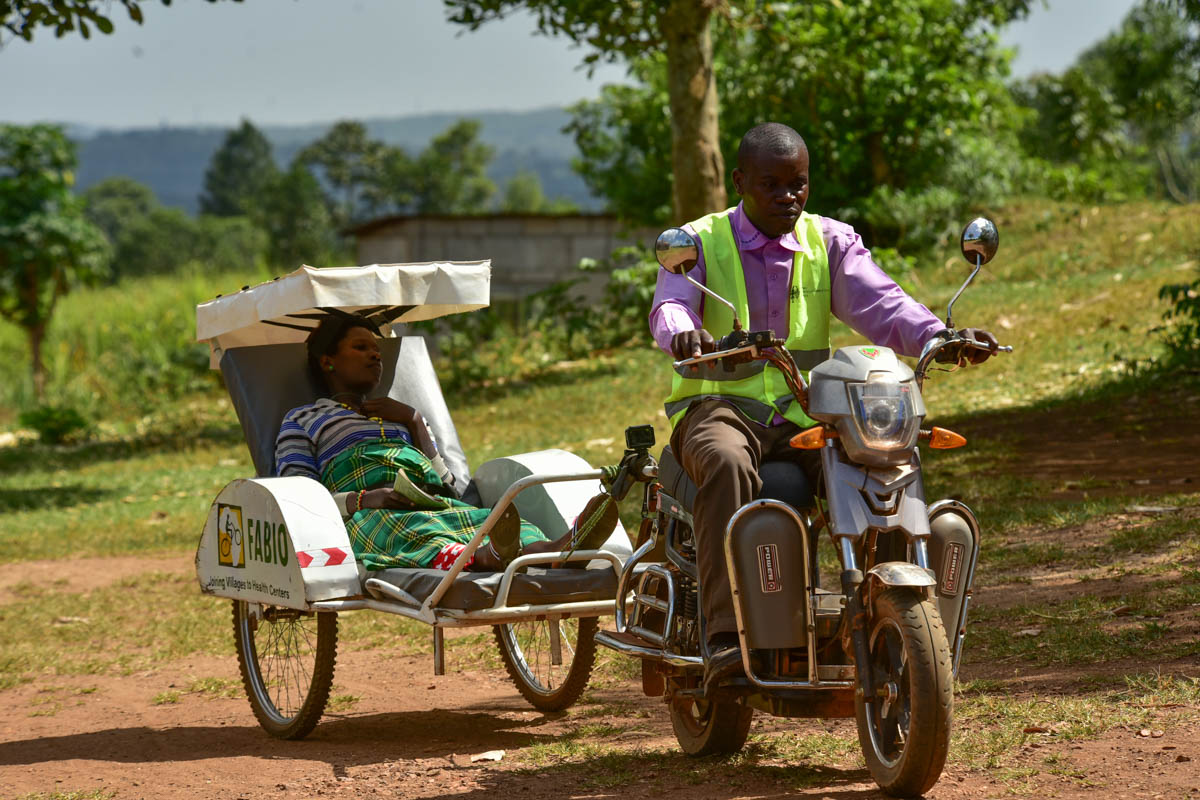 Where the terrain is hilly, the ambulances use rechargeable electric cycles. Pregnant women like Sandra Naigaga, who used to walk kilometres for care can now use the service.  [Nicholas Bamulanzeki/Al Jazeera]