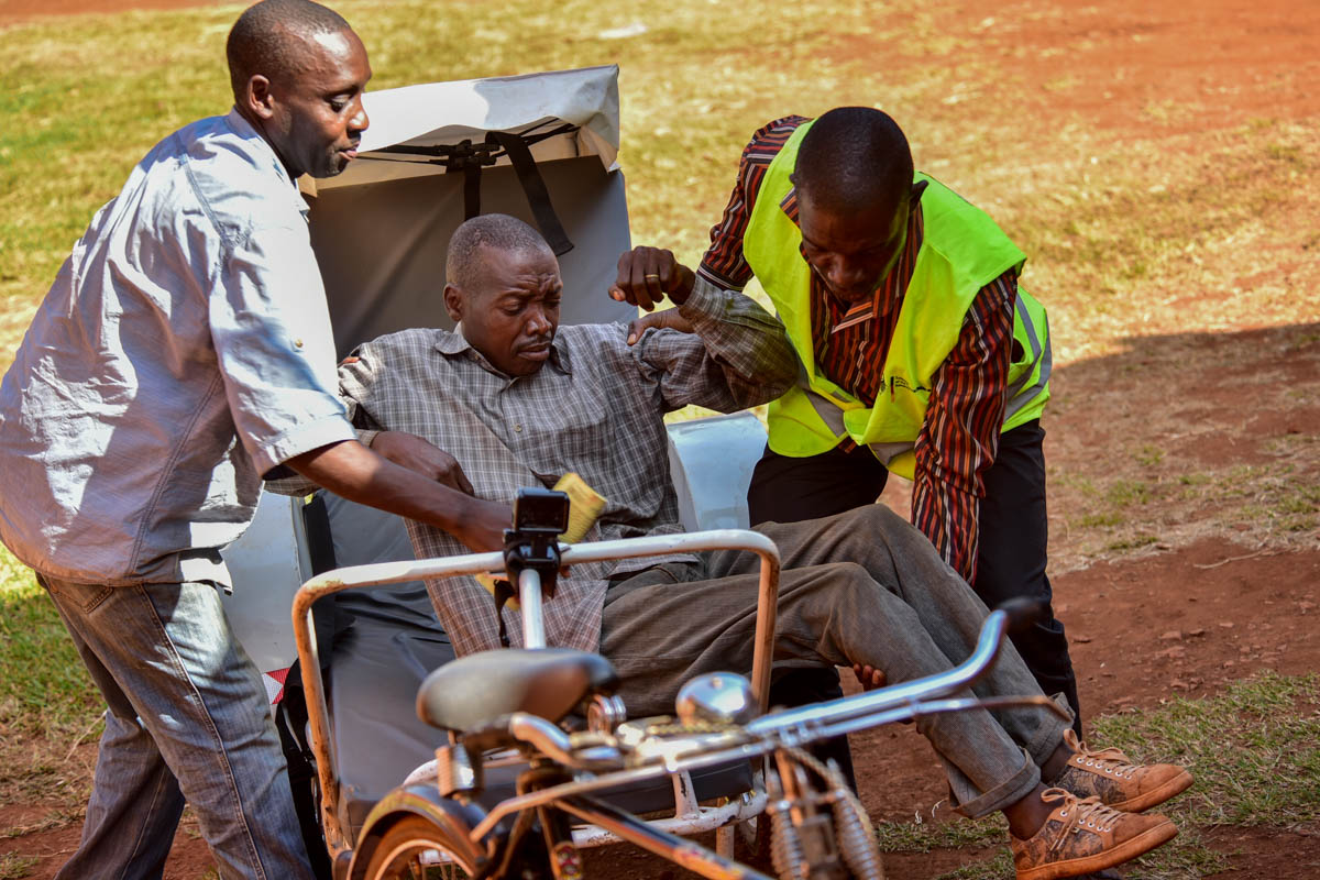 Harid Mukasa, a member of the Village Health Team with another man helps transfer a patient from the ambulance to a ward at Budondo health centre. In Uganda, fewer than 7 percent of patients arrive at health facilities by ambulance. [Nicholas Bamulanzeki/Al Jazeera]