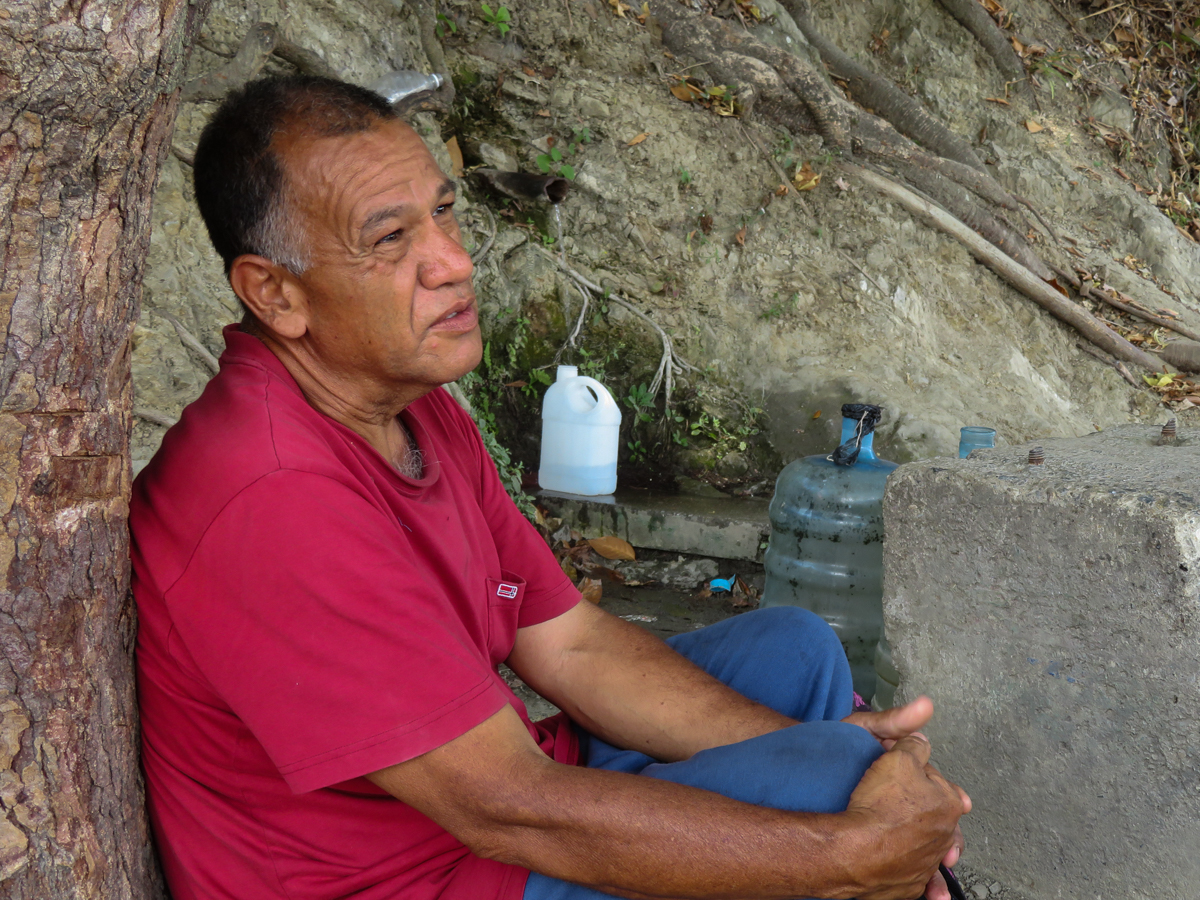 'I'm here to fill my little bucket, this water is clean, it is coming from the mountain, I'm exhausted from this situation, but we have to endure,' said Luis while waiting to get water. [Elizabeth Melimopoulos/Al Jazeera]