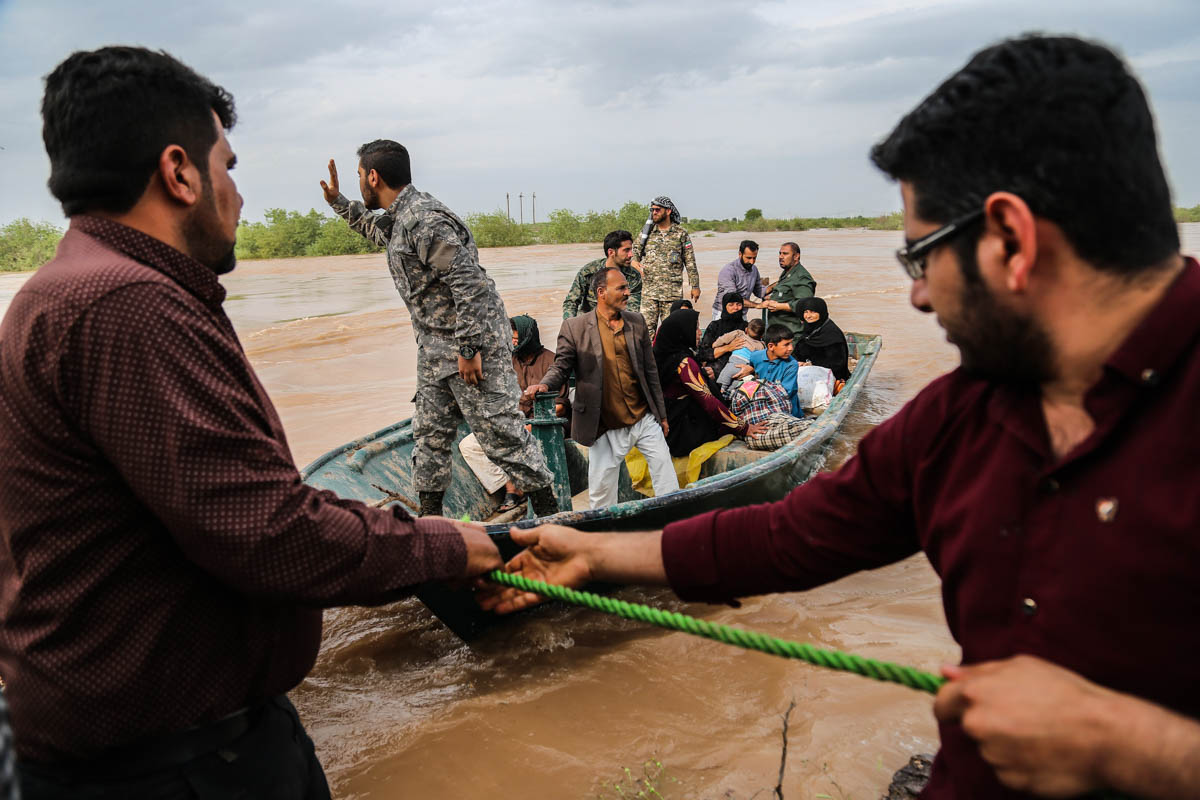 Iranian soldiers help civilians in a flooded area in a village around the city of Ahvaz, in Iran's Khuzestan province. [Mehdi Pedramkhoo/Tasnim News/AFP]
