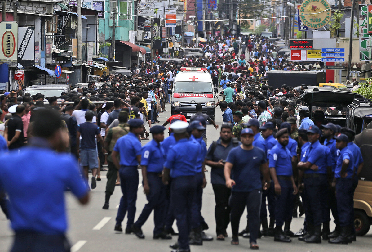 Sri Lankan police officers clear the road as an ambulance drives through carrying people injured in the blasts in Colombo. [Eranga Jayawardena/AP Photo]