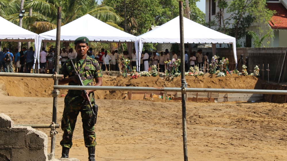 The mass funeral was guarded by members of Sri Lanka's armed forces [Kate Mayberry/Al Jazeera]