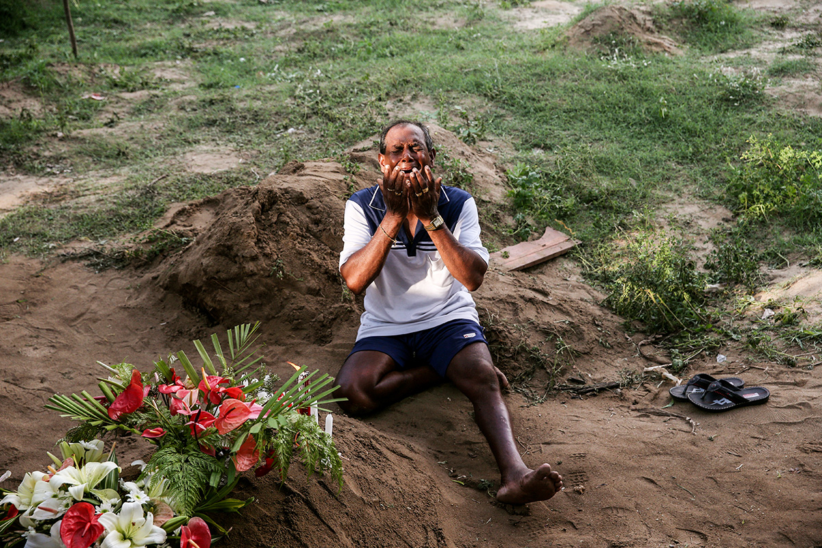 A man mourns at a grave of a victim, two days after a string of suicide bomb attacks on churches and luxury hotels. [Athit Perawongmetha/Reuters]