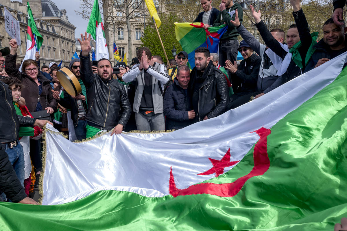 Algerians in the Place de la Republique  in Paris celebrate the resignation of Abdelaziz Bouteflika and demand the departure of key allies of the former president, who stepped down April 3. [Omar Havana/Al Jazeera]
