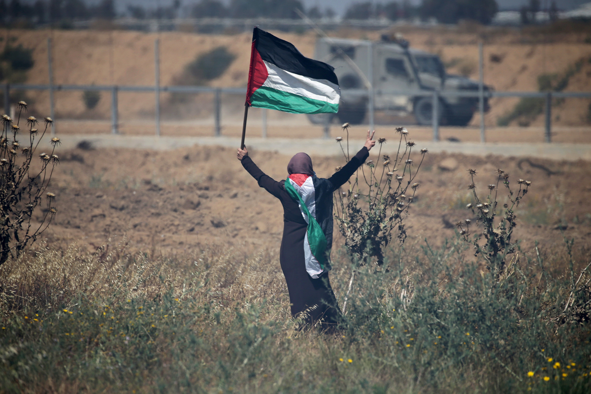 A Palestinian woman protesting at the separation fence in the southern Gaza Strip. [Ibraheem Abu Mustafa/Reuters]