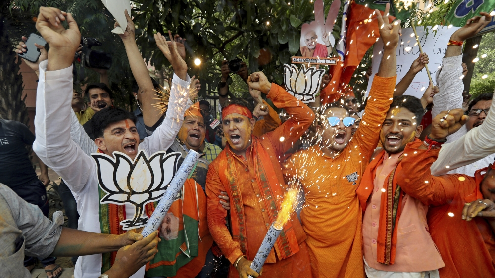 Bharatiya Janata Party (BJP) workers celebrate outside BJP headquarters in New Delhi India, Thursday, May 23, 2019. Indian Prime Minister Narendra Modi and his party have a commanding lead in early vo